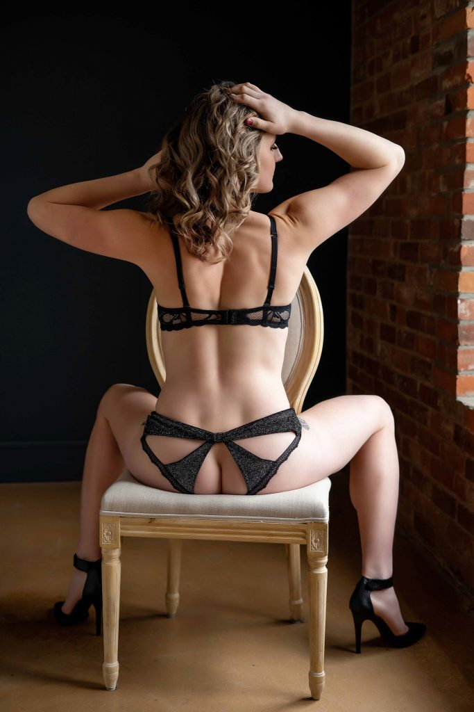Women photographed for boudoir session sitting on chair in black lingerie.