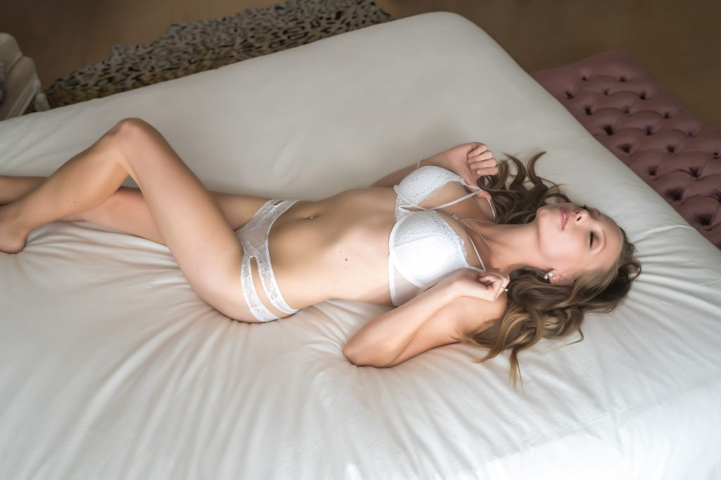 Woman lying on bed in white lingerie.