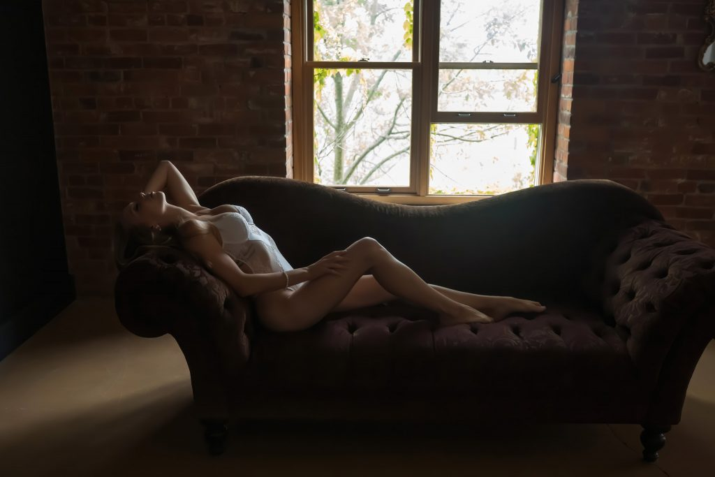 Woman in white body suite lying on couch during a boudoir suite.