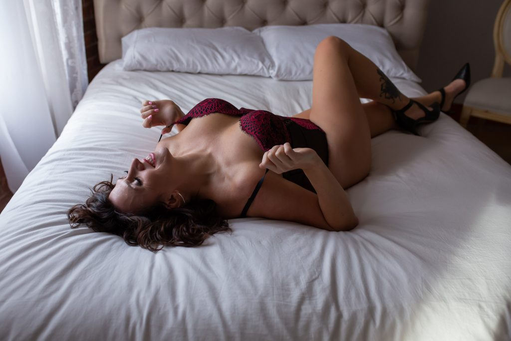 Woman smiling lying on bed modelling for a boudoir photography shoot.