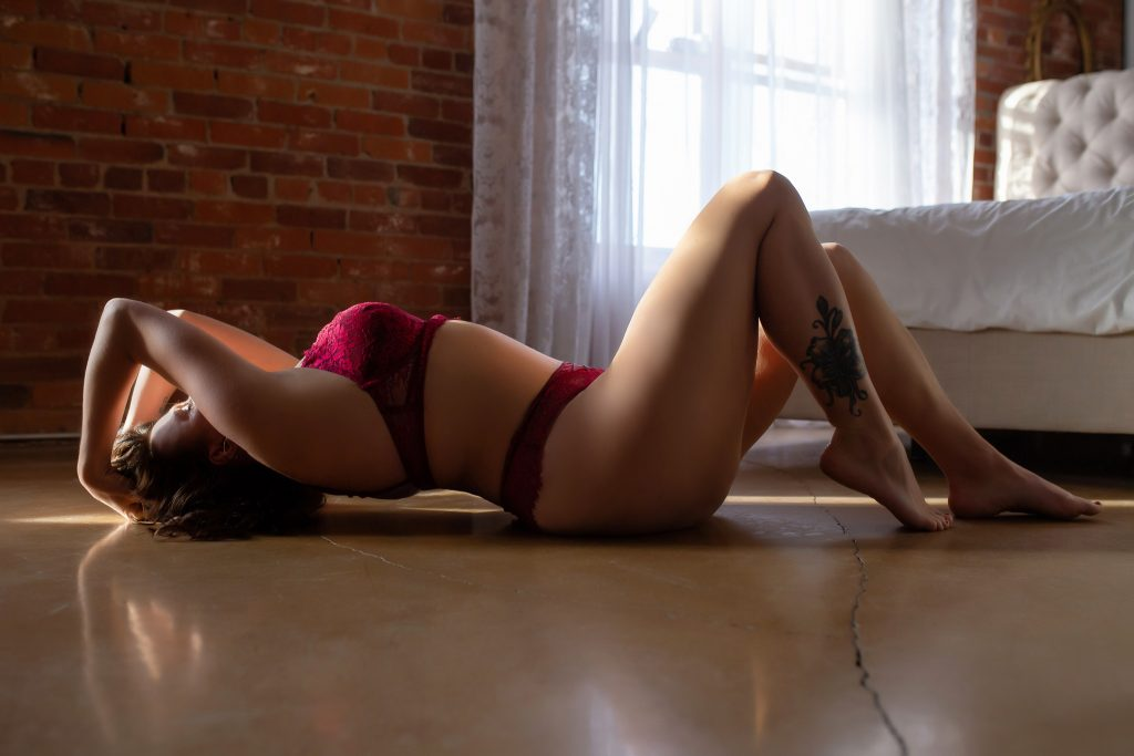 Woman modelling red lingerie in Victoria BC boudoir photography studio.