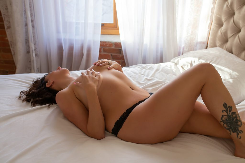 Woman lying on bed during boudoir photography shoot.