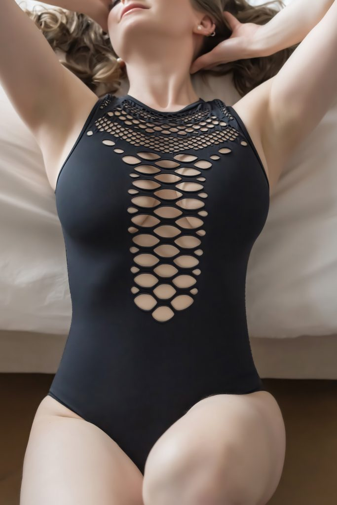 Woman posing the black body suite with mesh detailing.