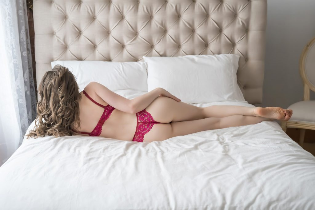 Woman posing on bed in Bella Boudoir studio.