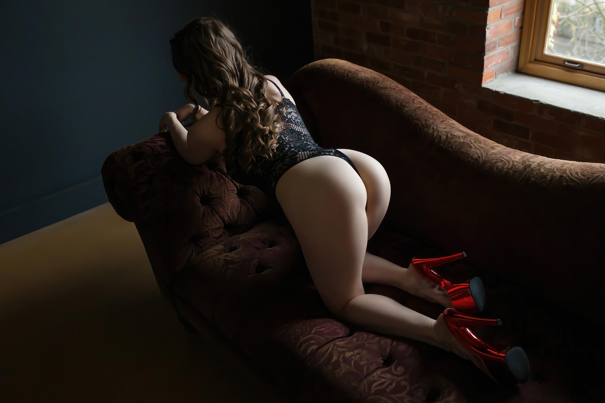 Woman posing for boudoir shoot wearing red heels.
