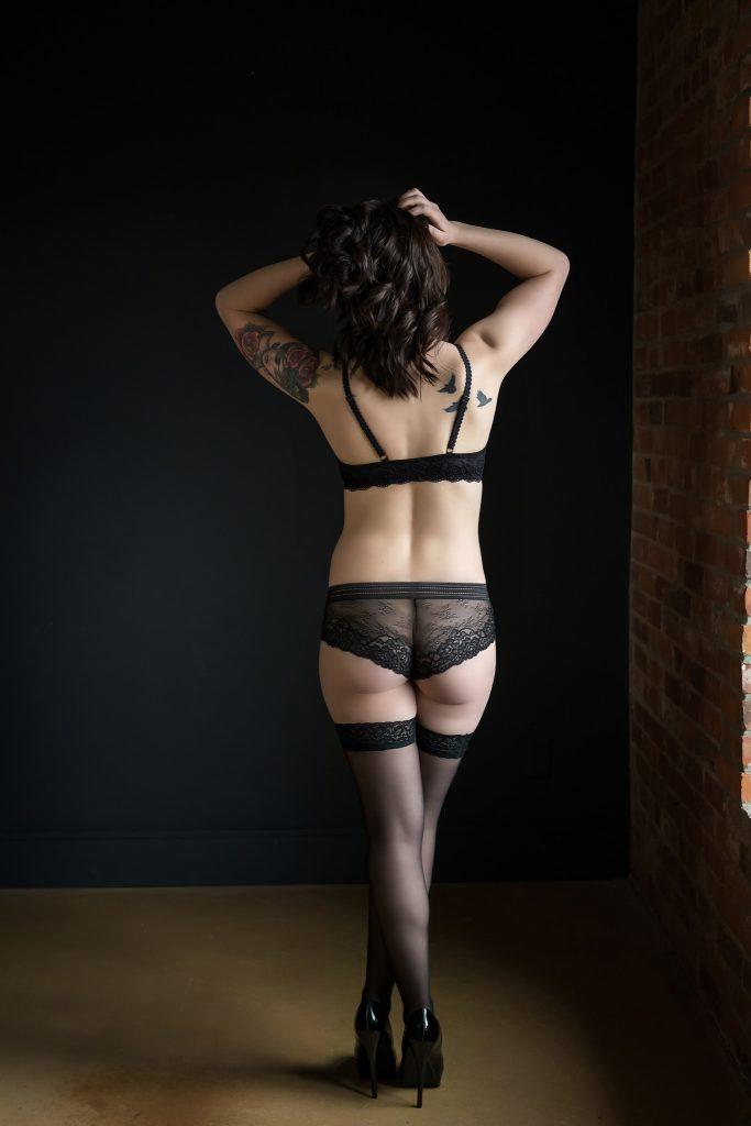 Standing boudoir pose in black lingerie.