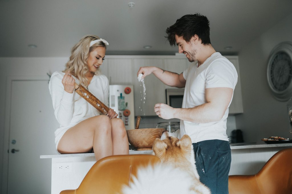 Couple playing with dog in kitchen