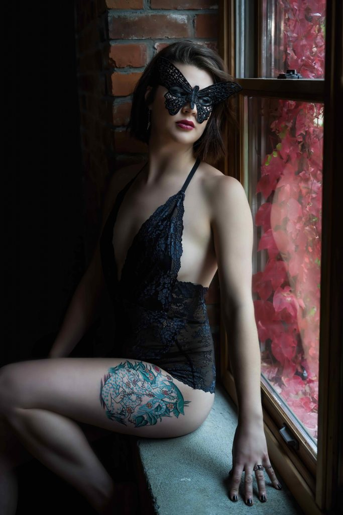 Masked boudoir pose by window