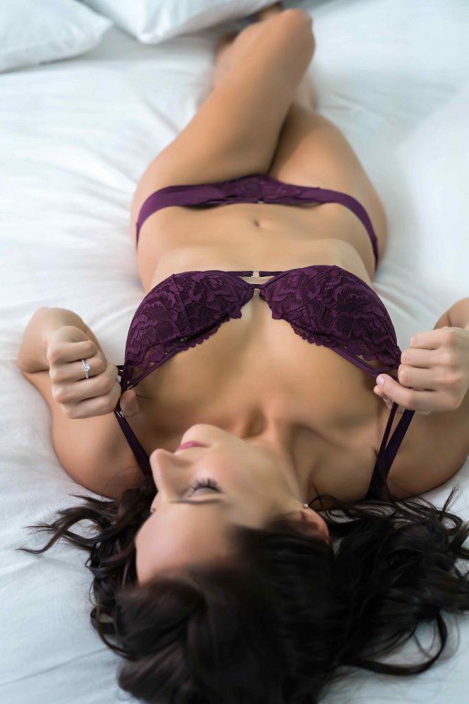 boudoir pose holding bra straps