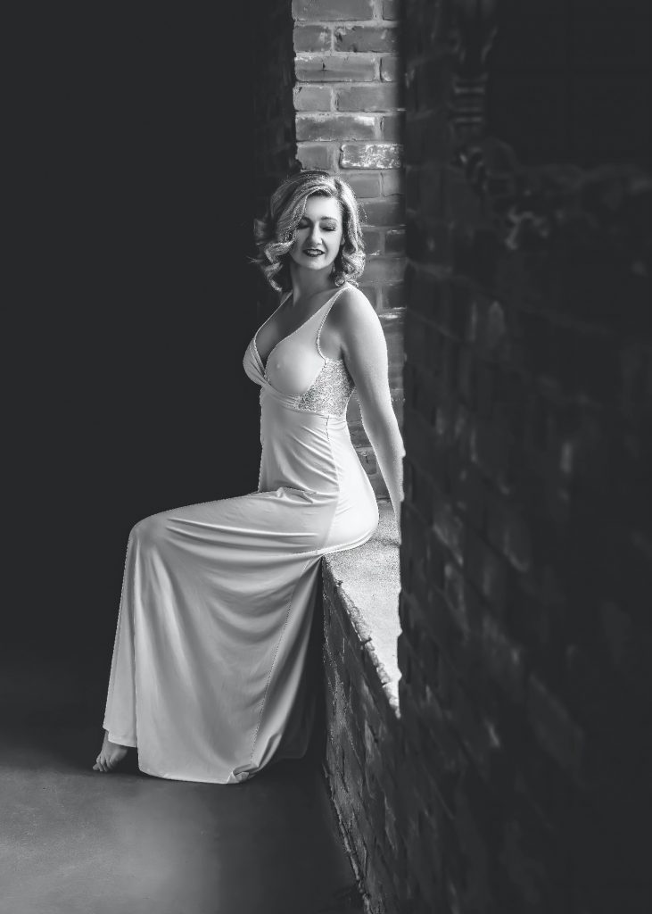 black and white image of woman posing in white dress
