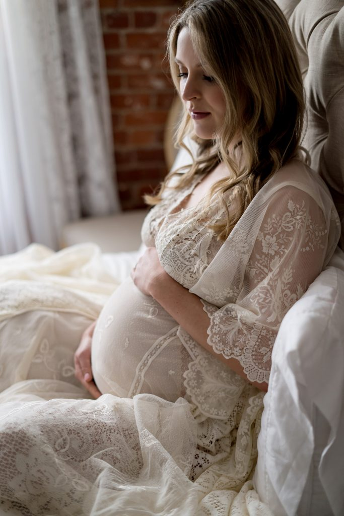 woman sitting in bed posing for maternity shoot