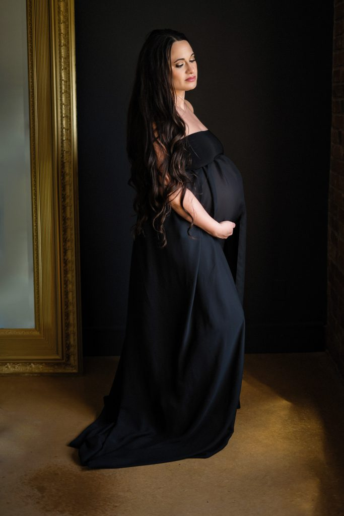 woman posing in black gown for boudoir maternity