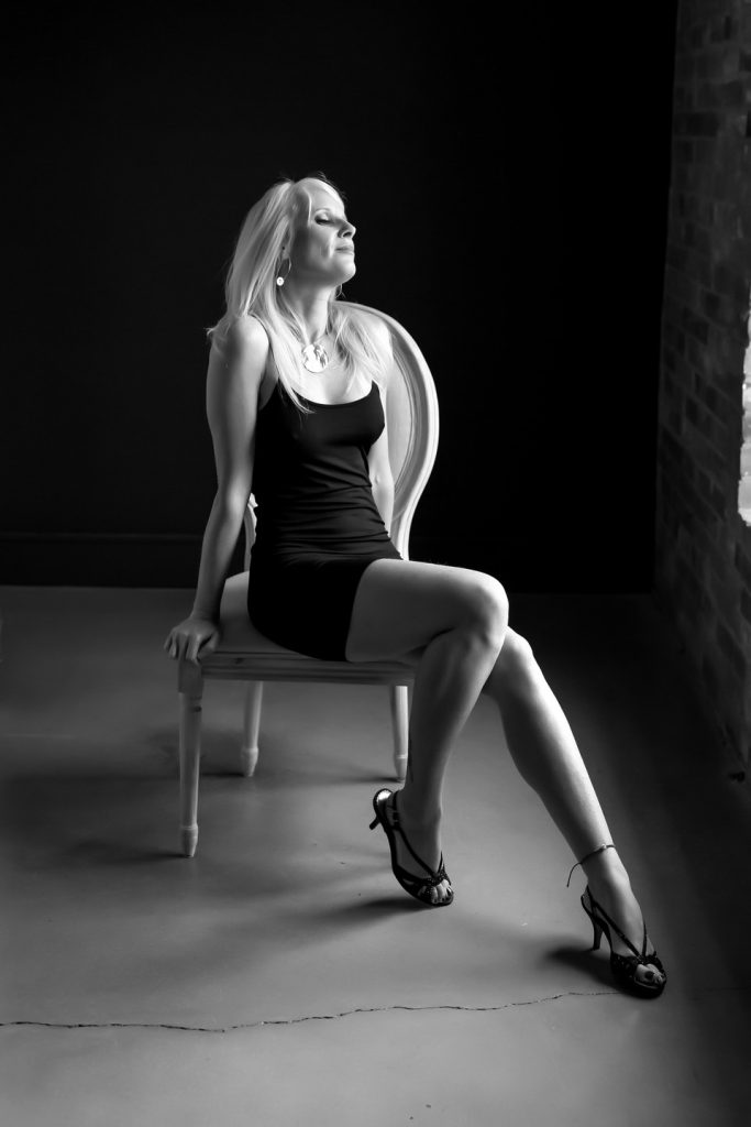 black and white image of woman posing in photography studio