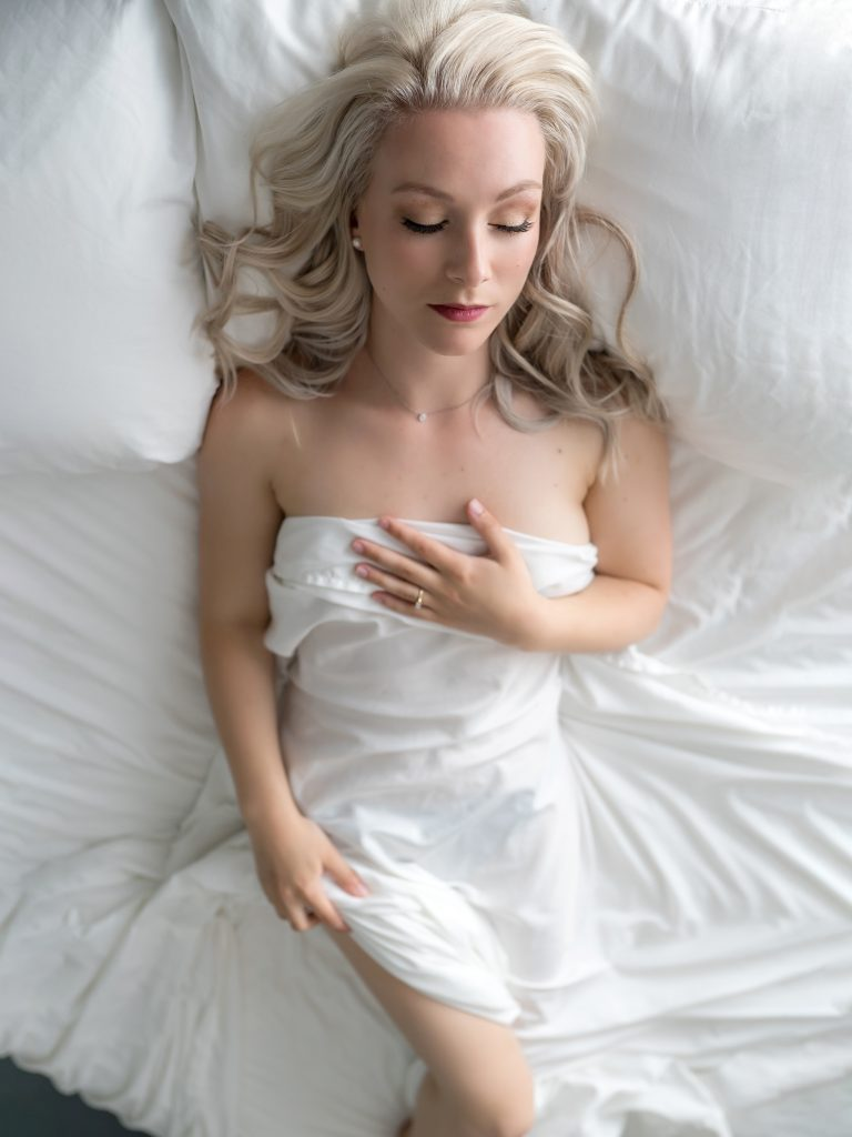 woman lying on bed with white sheet